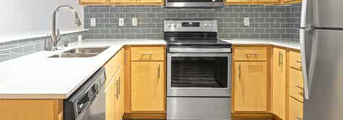 An updated AMLI 535 apartment kitchen area with a grey tiled back splash light cabinets and stainless steel appliances