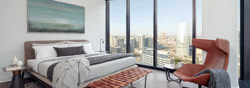 Interior of bedroom at AMLI Fountain Place with floor to ceiling windows with city views and creme walls with dark flooring