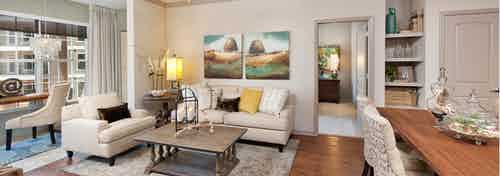 Living room at AMLI North Point with a large window and chestnut colored wood floors with neutral, elegant decor