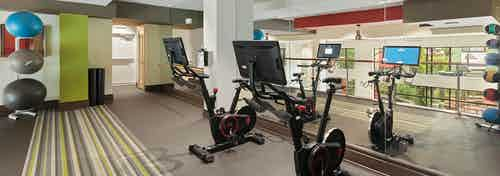 Upstairs interior of fitness center at AMLI Ponce Park with exercise bikes and medicine balls and floor to ceiling wall mirror