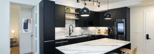 Interior of AMLI Midtown Miami apartment kitchen with marble island and three stools and dark cabinets and wood tile flooring