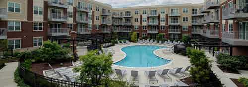 Courtyard at AMLI Deerfield with in ground pool surrounded by lounge chairs and BBQ grilling stations with a firepit