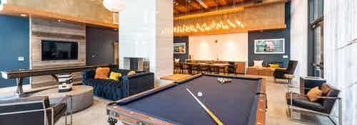 Interior of clubhouse with shuffle board, pool table and elegant blue couch and pendant light AMLI Marina Del Rey apartments
