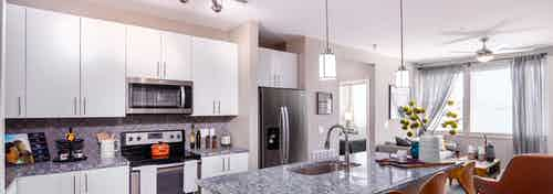 Interior of AMLI Littleton Village apartment kitchen with granite countertops, stainless steel appliances and white cabinetry