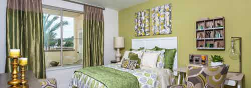 Interior view of AMLI Spanish Hills bedroom with queen bed and white headboard facing large window with green satin curtains