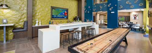 Clubroom at AMLI Buckhead with yellow and blue textured walls and booth seating with a white counter and industrial barstools