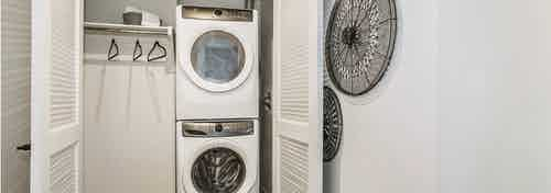 View of full sized front loading stacked washer and dryer closet with laundry hanging rod at AMLI Marina Del Rey apartments