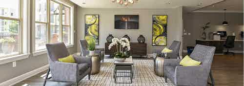 AMLI Lindbergh resident lounge with four patterned chairs and yellow decor accents with large windows facing landscape