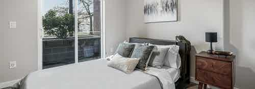 AMLI Bellevue Park apartment bedroom with white and grey bed and brown nightstand and sliding glass door to patio
