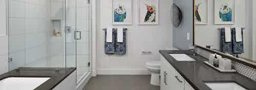 Interior of AMLI Marina Del Rey bathroom with quartz countertop, standing shower with frameless doors, tub and tile flooring