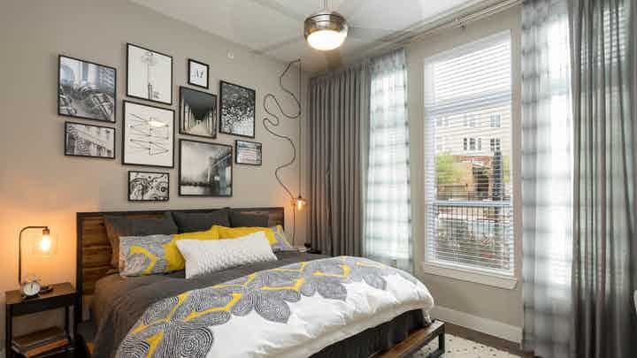 Interior view of AMLI Frisco Crossing apartment bedroom with bed and nightstands and large window with blinds and curtains