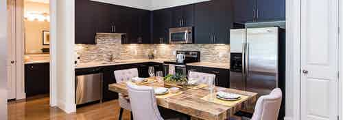 Interior view of AMLI RidgeGate dining area with table fully set and kitchen with dark cabinets and mosaic tile backsplash