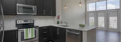 AMLI Buckhead kitchen with black cabinets and white countertops with modern light fixtures and stainless steel appliances