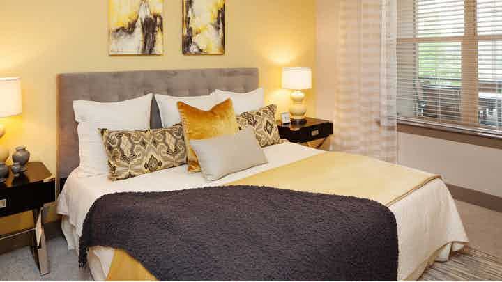 Bedroom at AMLI on Maple with a large white, yellow and brown bed against a yellow accent wall with a window to the right