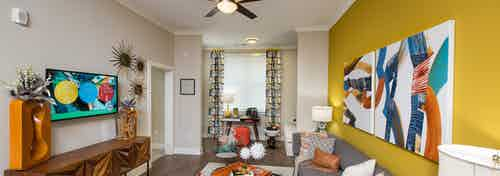 AMLI Buckhead living room with wood floors and a mustard yellow accent wall with bold modern styled orange and blue decor