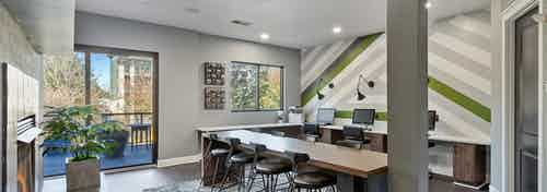 Interior view of AMLI Parkside cyber café with striped accent wall and long desks with computers and chairs and a gray pillar