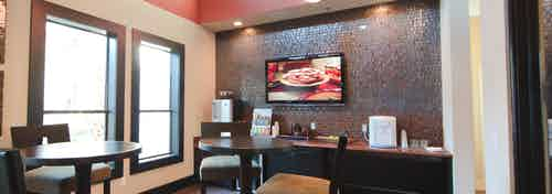 Interior view of java cafe at AMLI at Escena apartments with coffee serving bar and tables and chairs and big screen TV