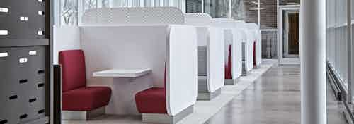 Interior view of the cyber lounge at AMLI Lofts apartment community that has crisp white booths paired with bright red seats