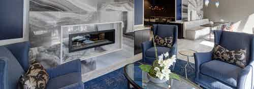Lounge at AMLI Deerfield with a large marble fireplace and blue seating with tables and gourmet kitchen in background