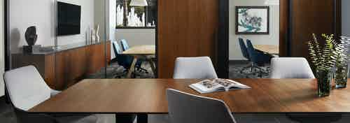 Co working area at AMLI Fountain Place apartments with wood table and chairs and sliding doors with view of private offices