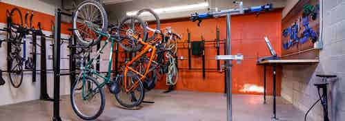Interior of AMLI Littleton Village Bike/ski/snowboard repair room with orange walls, bike racks and tools and work counter