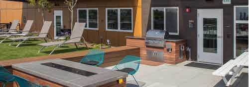 One of three rooftop decks at AMLI Wallingford with BBQ fire pit lounge seating and turf grass for lawn games