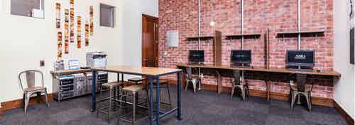 A business center at AMLI Park Avenue apartments with computers and chairs up against a brick wall with a printer and table