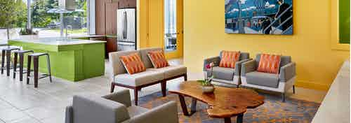 AMLI at Mueller clubroom with grey couches and chairs against a yellow wall with barstools at a green counter in background