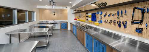 DIY maker space at AMLI Decatur with tools on peg wall and lockers with a sink as well as work areas for residents to create