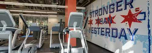 Fitness center with cardio machines and exposed overhead ductwork and a motivational mural at AMLI 900 apartment building