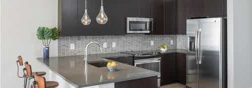 Interior of AMLI Arts Center Kitchen with black cabinets and stainless steel appliances with a grey patterned backsplash
