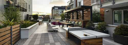 Outdoor gaming courtyard at duck with wood paneling on side of building and ping pong table and seating at AMLI Park Broadway