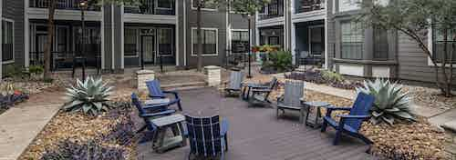 Day view of courtyard at AMLI Eastside apartments with gray and blue Adirondack chairs on a deck with trees and landscaping