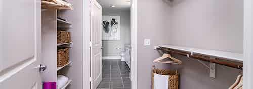 Interior of AMLI Littleton Village apartment's walk-in closet with shelving, wicker laundry hamper and peek into bathroom
