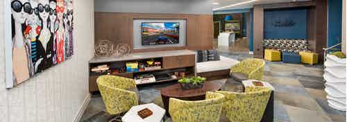 Clubroom at AMLI Buckhead with patterned yellow chairs and an entertainment center with a flat screen TV hanging above it