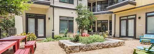 Close up of raised garden in the courtyard at AMLI 5350 with green leaves blooming and building facade in the background