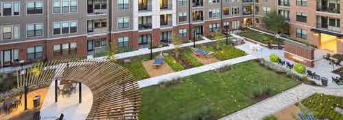 Aerial view of AMLI Addison lushly landscaped courtyard with string lights and hammocks and pergola and seating throughout