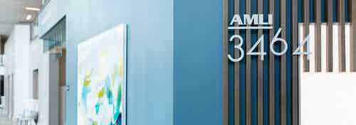 Interior view of the lobby at AMLI 3464 apartment community with light blue walls and an abstract art wall hanging
