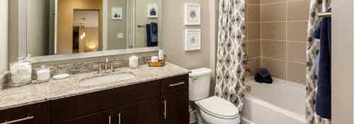 AMLI West Plano bathroom with dark wood vanity sink with a granite countertop and showertub with large beige wall tiles