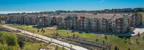 Daytime aerial view of AMLI at Interlocken apartment community perched on a grassy hill with walking paths and a blue sky
