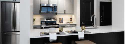 Interior of kitchen at AMLI Quadrangle with grey wood cabinets and a black island with white countertops and beige backsplash