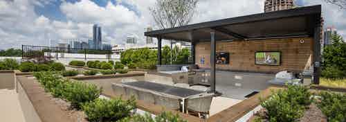 Exterior view of AMLI Lenox rooftop grill area on a bright and sunny day with two grills and two televisions and dining area