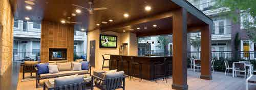 Nighttime view of cabana at AMLI Frisco Crossing apartments with serving bar with chairs, big screen TV and seating areas