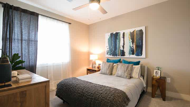 A bedroom at AMLI Dry Creek apartments with gray and blue linens and a dressers with plants and a painting and large window
