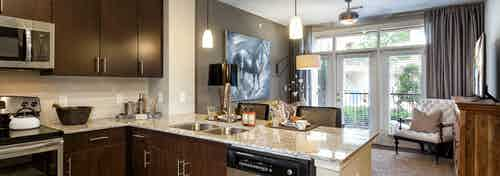 Interior of AMLI Campion Trail apartment kitchen with dark wood cabinets and stainless steel appliances and living room