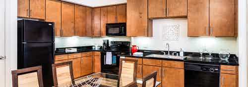 A kitchen at AMLI Park Avenue apartments with a dining table and dishwasher and sink and fridge and microwave and cabinets