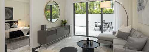 Interior view of AMLI Midtown Miami living room with sofa and two chairs and view of patio and peek into the bedroom