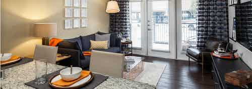 View of AMLI West Plano living room from kitchen island with dark hardwood and balcony doors with black and orange decor