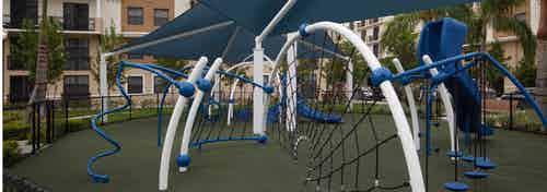 Modern Children's covered playground at AMLI Dadeland with blue and white recreational equipment on faux grass foundation