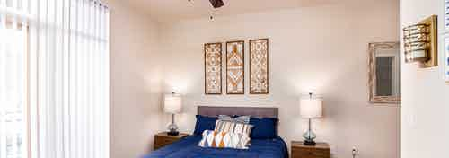 A bedroom at AMLI Arista apartments showcasing a bed with blue sheets and artwork hanging and a window with blinds drawn